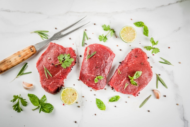 Fresh raw meat. beef tenderloin, steaks, on a white marble table. with olive oil, spices for cooking - basil, rosemary, coriander, parsley, garlic, lemon, salt, pepper. copy space top view