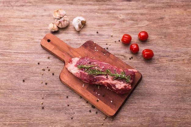 Свежее сырое мясо для стейка на деревянной разделочной доске, крупный план.