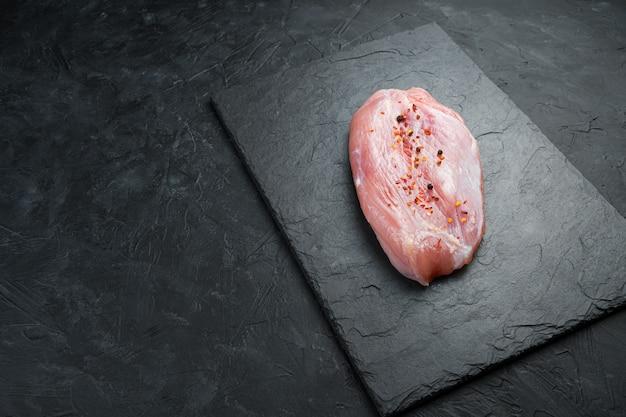 검정색 배경에 신선한 생고기입니다. 칠면조 필레 한 조각. 복사 공간 측면보기.