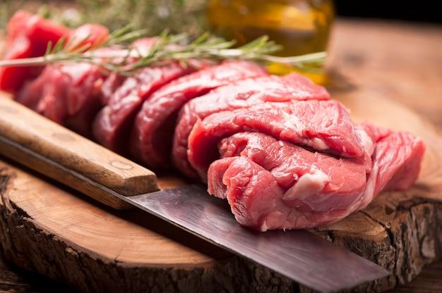 Свежее сырое мясо на старом деревянном столе