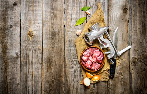 Fresh raw meat in a onion with chopper, knife and spices on old fabric. on a wooden table. free space for text . top view