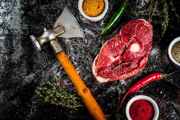 Fresh raw meat a piece of lamb's tenderloin with a bone with a cutting ax with spices for cooking on an old rusty black metal table