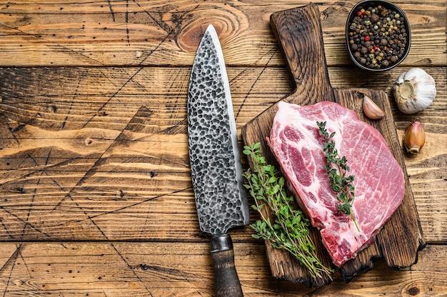 Стейки из свежего сырого мяса из свинины на разделочной доске с ножом