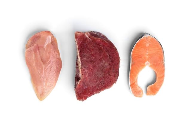 白い背景で隔離の新鮮な生肉、サーモン、鶏の切り身。たんぱく質を多く含む天然食品。