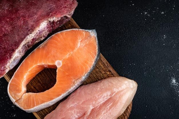 黒の背景に木製まな板に新鮮な生肉、サーモン、鶏の切り身。たんぱく質を多く含む天然食品。上面図。