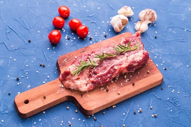 Fresh raw meat for steak on wooden cutting board.