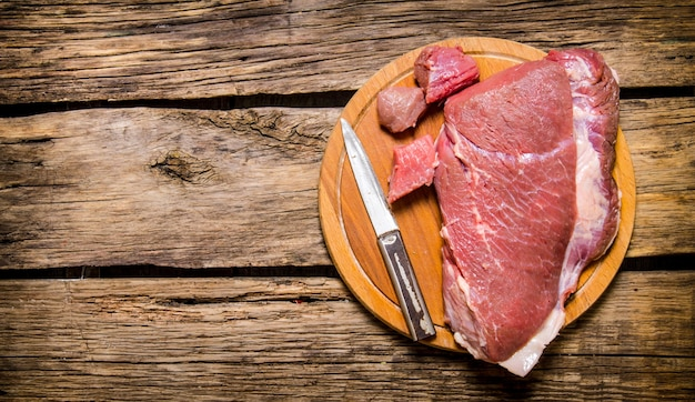 Fresh raw meat with a butcher knife on wooden background