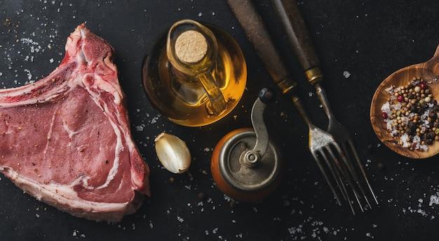 Свежее сырое мясо со специями и солью на темном деревенском.
