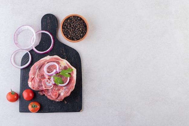 石のテーブルに置かれた野菜とコショウのトウモロコシと新鮮な生肉。
