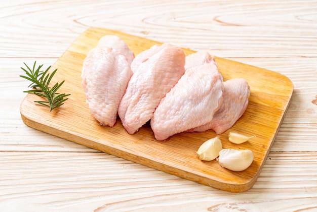 목 판에 신선한 생 중간 닭 날개