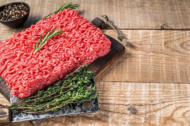 肉屋のまな板に包丁を添えた新鮮な生のミンチビーフ肉。木製の背景。上面図。スペースをコピーします。