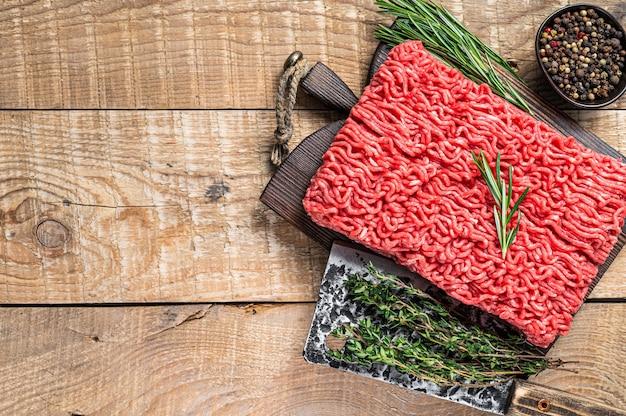 Свежее сырое мясо говядины фарша на разделочной доске мясника с тесаком. деревянный