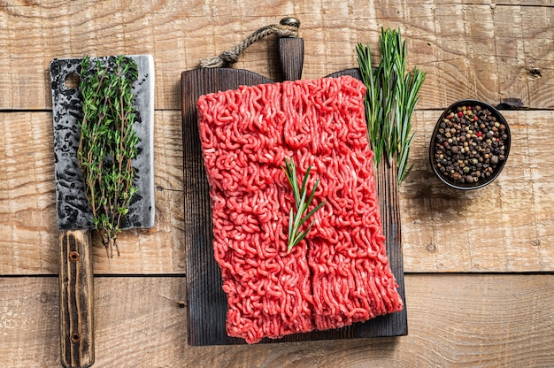 Свежий сырой фарш из говядины на разделочной доске мясника с тесаком