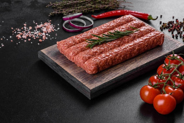 Fresh raw mince for grilled kebab with spices and herbs on a dark concrete table