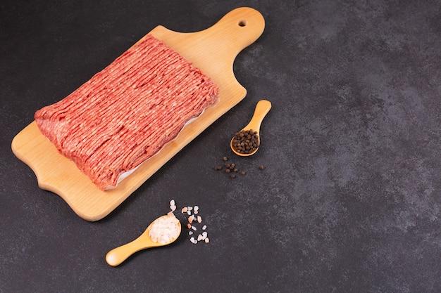 Свежий сырой фарш из свинины на бумажной основе и разделочной доске