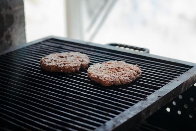 그릴에 향신료와 신선한 원시 다진 된 쇠고기 스테이크 햄버거.