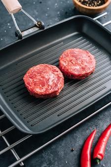 칠리 페퍼와 검은 그릴 팬에 햄버거를위한 신선한 생 다진 쇠고기 스테이크