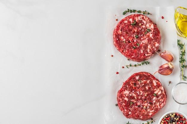 白い背景で調理するためのスパイスとハーブと白い背景の新鮮な生のミンチ肉ビーフバーガーパティ。上面図