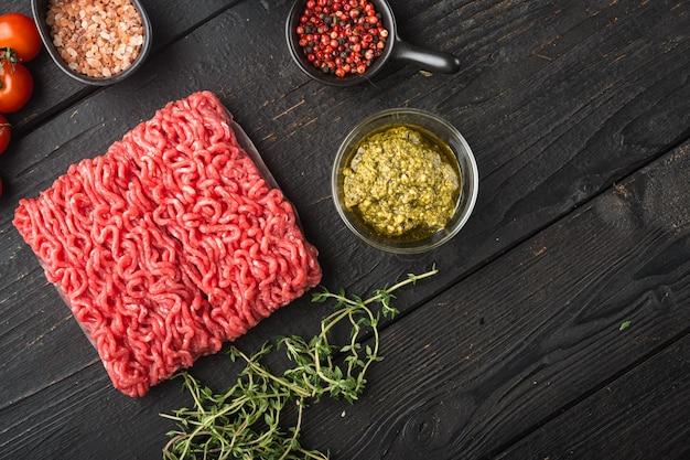 ミートボール用の新鮮な生のミンチ肉、スパイスペッパー、塩、モッツァレラチーズ、ペストセット、黒い木製のテーブル、上面図フラットレイ