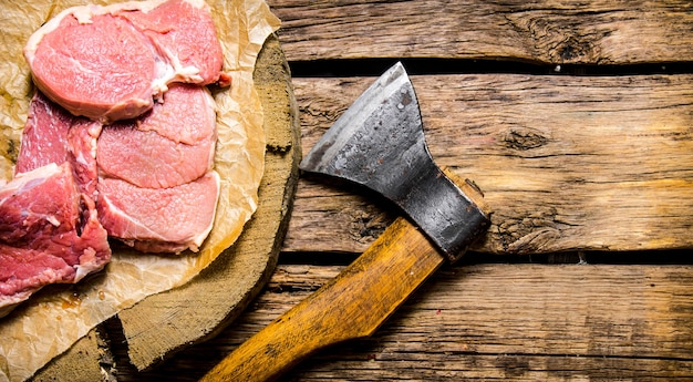 Fresh raw minced meat with an axe on a wooden table