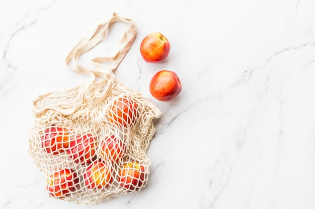 Fresh raw nectarines lying in string bag on white marble