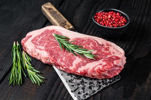 肉屋の肉切り包丁に新鮮な生のニューヨークストリップビーフステーキ