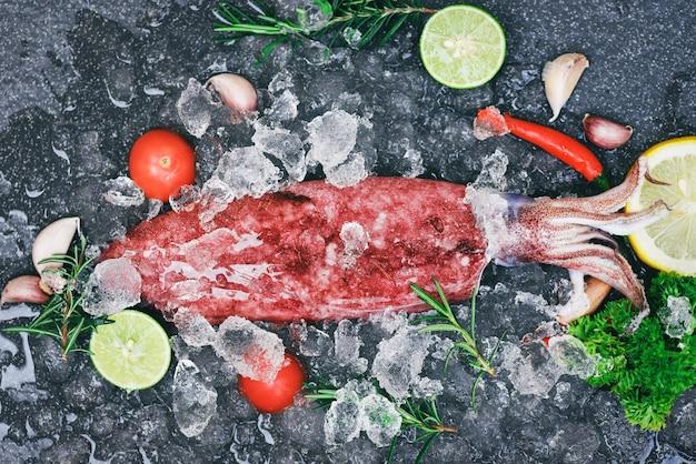 Свежие сырые каракатицы из осьминога океанского гурмана с лимоном и розмарином на темной тарелке
