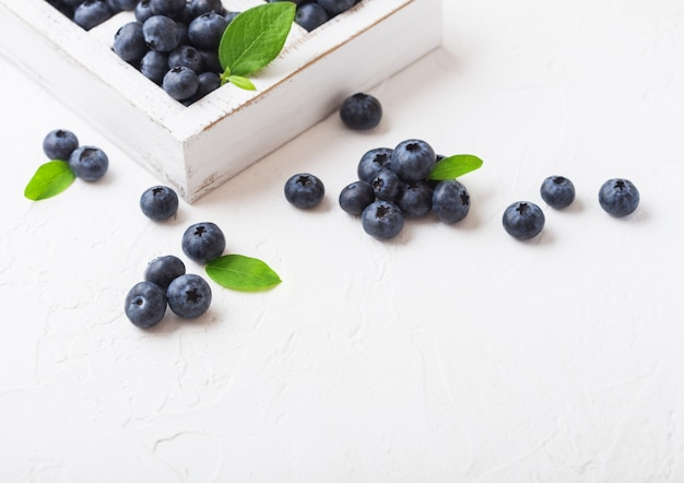 Fresh raw organic blueberries with leaf in vintage wooden box on kitchen background.