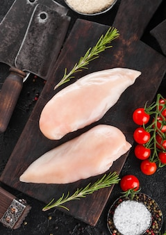 Fresh raw organic chicken fillet breast on vintage board with meat hatchets