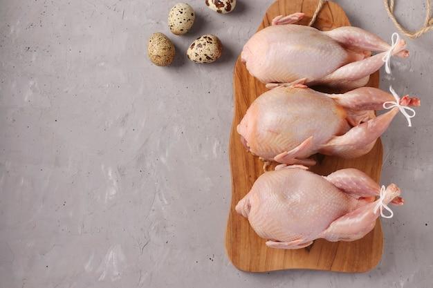 Fresh raw organic quails on wooden board and quail eggs