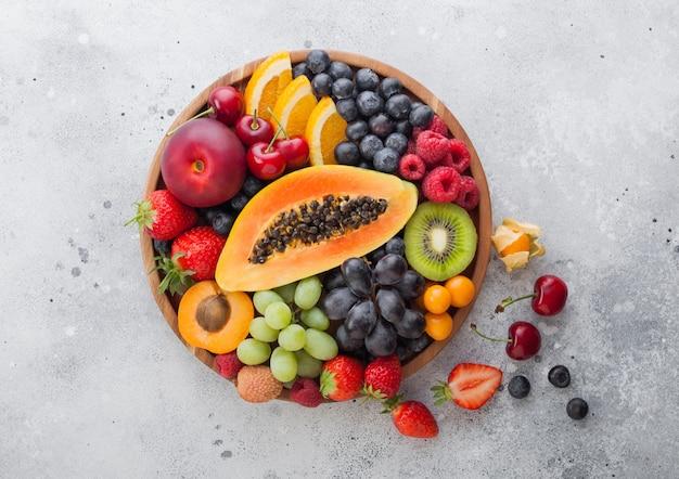 明るいキッチンの背景に丸い木のプレートで新鮮な生の有機夏のベリーとエキゾチックなフルーツ。パパイヤ、ブドウ、ネクタリン、オレンジ、ラズベリー、キウイ、イチゴ、ライチ、チェリー。上面図