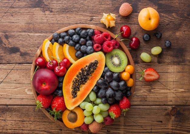 木製のキッチンの背景に丸い木のプレートで新鮮な生の有機夏のベリーとエキゾチックなフルーツ。パパイヤ、ブドウ、ネクタリン、オレンジ、ラズベリー、キウイ、イチゴ、ライチ、チェリー。上面図