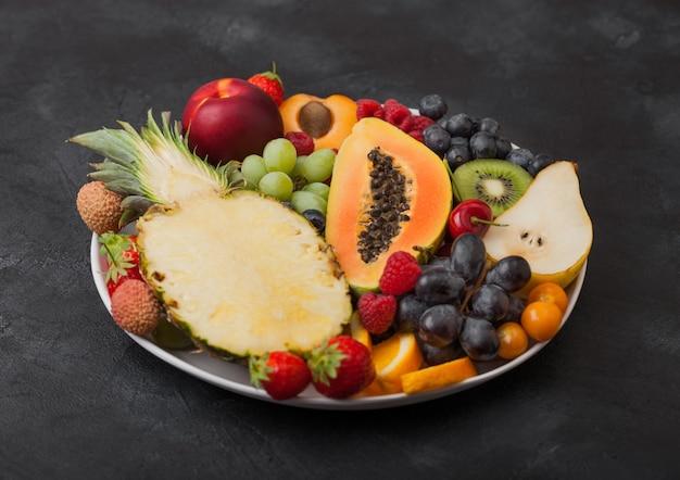 黒の背景に白いプレートで新鮮な生の有機夏のベリーとエキゾチックなフルーツ。パイナップル、パパイヤ、ブドウ、ネクタリン、オレンジ、アプリコット、キウイ、ナシ、ライチ、チェリー、サイサリス。上面図
