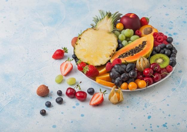 青いキッチンの背景に白いプレートで新鮮な生の有機夏のベリーとエキゾチックなフルーツ。