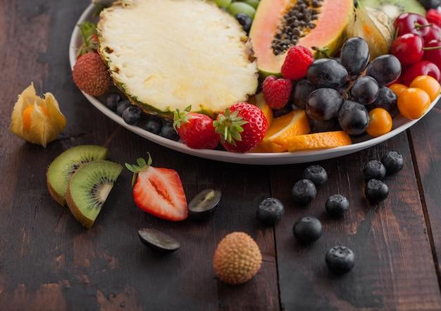 ダークウッドの背景に白いプレートで新鮮な生の有機夏のベリーとエキゾチックなフルーツ。パイナップル、パパイヤ、ブドウ、ネクタリン、オレンジ、アプリコット、キウイ、イチゴ、ライチ、チェリー。上面図