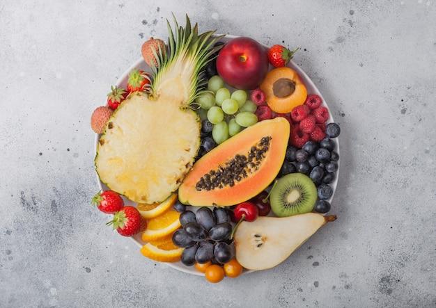 明るい背景の白いプレートに新鮮な生の有機夏のベリーとエキゾチックなフルーツ。パイナップル、パパイヤ、ブドウ、ネクタリン、オレンジ、アプリコット、キウイ、ナシ、ライチ、チェリー、サイサリス。上面図