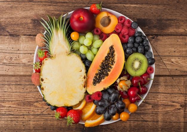 ヴィンテージの木製の背景に白いプレートで新鮮な生の有機夏のベリーとエキゾチックなフルーツ。パイナップル、パパイヤ、ブドウ、ネクタリン、オレンジ、アプリコット、キウイ、イチゴ、ライチ、チェリー。上面図