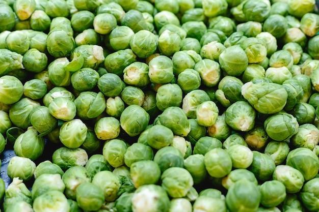 新鮮な生のオーガニック生ブリュッセルもやし野菜をファーマーズマーケットで販売しています。ビーガンフードと健康的な栄養の概念。