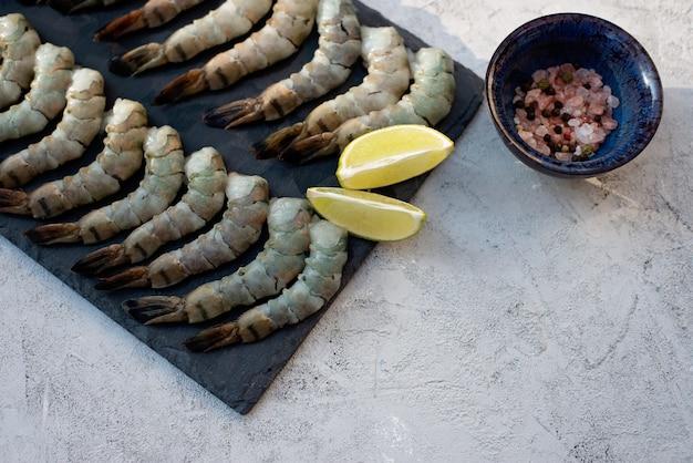 新鮮な生の皮をむいたエビとスパイスとレモンの石板。健康的なシーフードはタンパク質の源です。フラット横たわっていた。