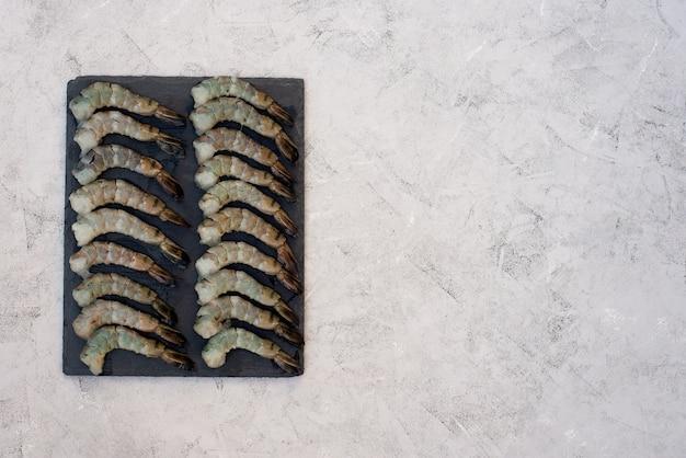 石板に新鮮な生皮をむいたエビ。健康的なシーフードはタンパク質の源です。フラット横たわっていた。コピースペース。