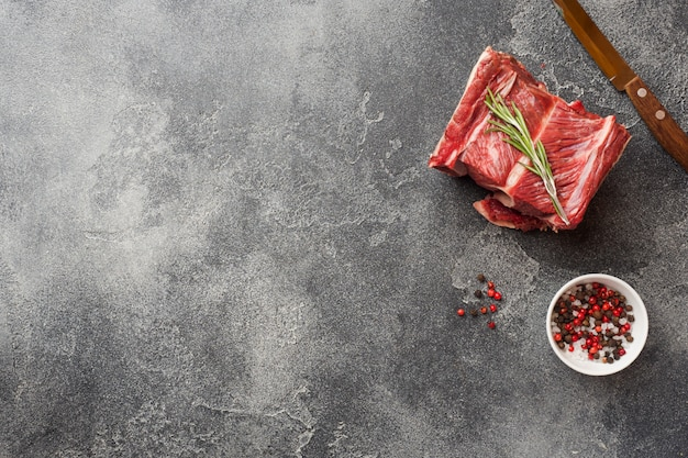 Fresh raw piece of beef rib with meat on a dark concrete surface