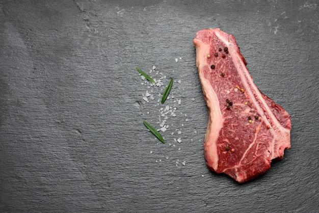 쇠고기 고기의 신선한 원시 조각, striploin 스테이크는 향신료와 함께 블랙 보드에 놓여 있습니다.