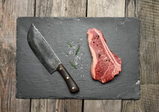 Свежий сырой кусок говяжьего мяса, стейк на деревянной поверхности, вид сверху