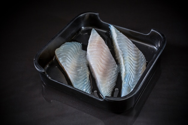 Fresh raw pieces pangasius dolly fish in tray on black background, fresh fish, raw fish