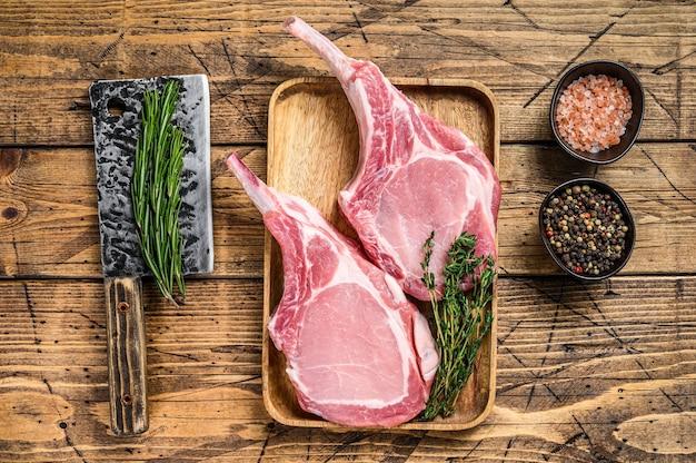 Свежие сырые отбивные из свинины с перцем и солью