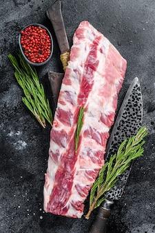 칼으로 커팅 보드에 향신료와 신선한 원시 돼지 고기 랙 갈비.