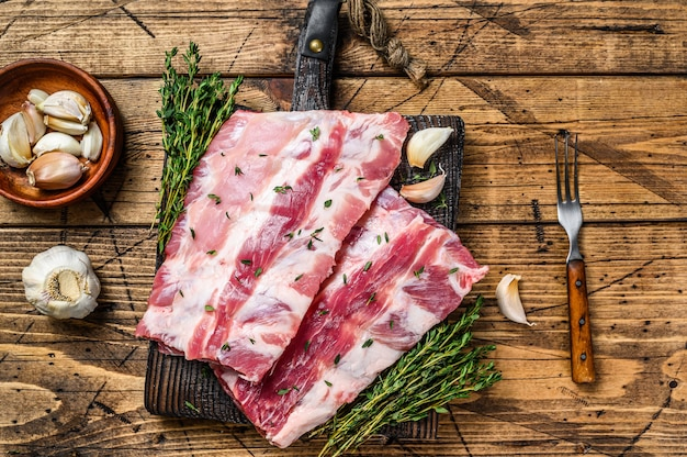 도마에 백리향과 마늘을 곁들인 신선한 생 돼지 고기 랙 갈비. 프리미엄 사진