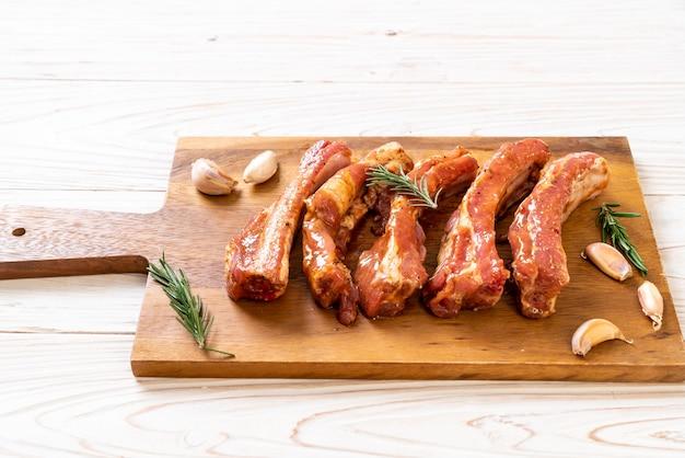 Свежие сырые свиные ребрышки готовы к запеканию с ингредиентами на деревянной доске