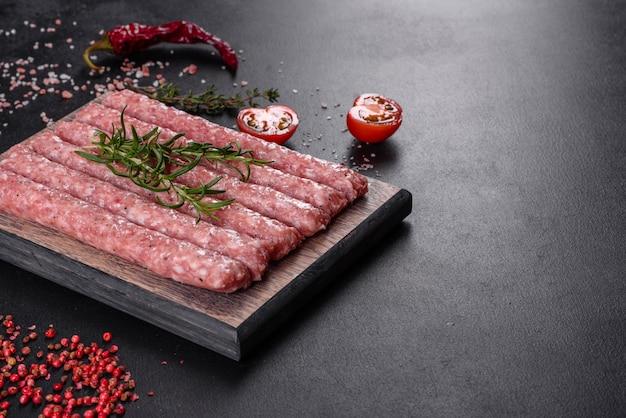 Свежие сырые свиные колбаски со специями на деревянной разделочной доске на бетоне