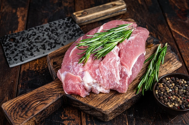 Свежие сырые свиные лопатки вырезать с ингредиентами и специями на кухонном столе. темный деревянный стол. вид сверху.